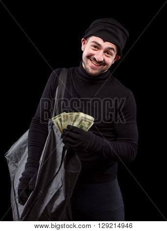 Burglar is carying full bag of money and smiling for camera over dark grey background. Handsome gangster after burglary of house, apartment or flat. Isolated on black.