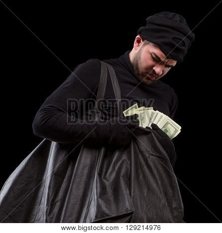 Thief carrying bag with much money and counting it over black background. Masked thief after robbery or burglary. Isolated on black.