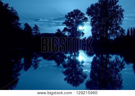 Blue moody view on bayou river during late night after sunset