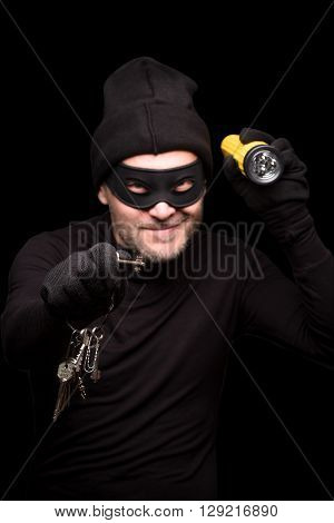 Burglar in black balaclava with flashlight and keys at night. Handsome man going to do robbery or burglary of house. Isolated on black.