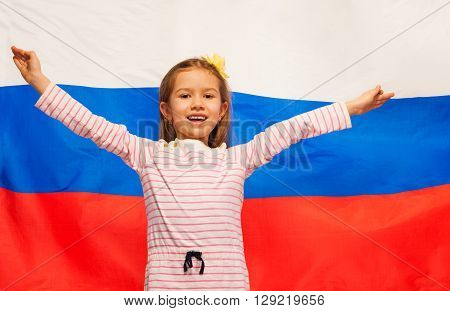 Smiling girl raising her hands up standing against the flag of Russian Federation