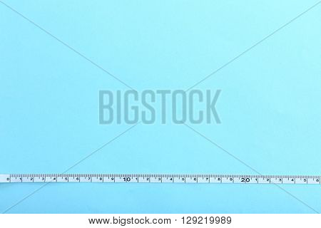 White measuring tape on a blue background