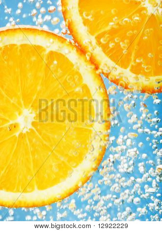 Fresh orange dropped into water with bubbles