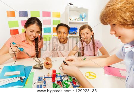 Teenage student, Asian girl, soldering component onto circuit board of electronic constructor