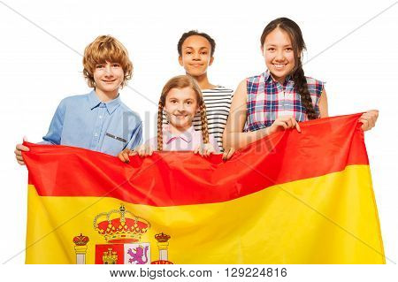 Group of four happy multiethnic teenage kids with flag of Spain, isolated on white