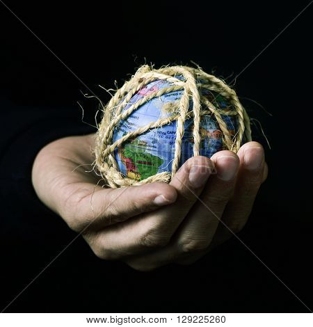 closeup of a young man with a world globe in his hand tied with rope, with a dramatic effect