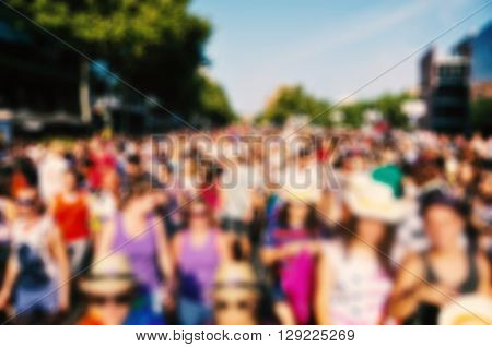 defocused background of a crowd of people partying or marching in a protest or in a parade outdoors