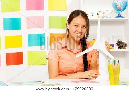Asian student, beautiful teenage girl, sitting at the class with model of wind power generator