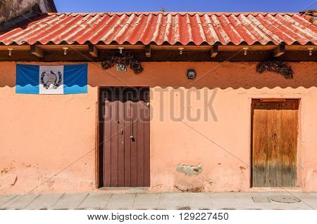 Antigua Guatemala - October 5 2014: Old painted house adorned with Guatemalan flag in colonial city & UNESCO World Heritage Site of Antigua.