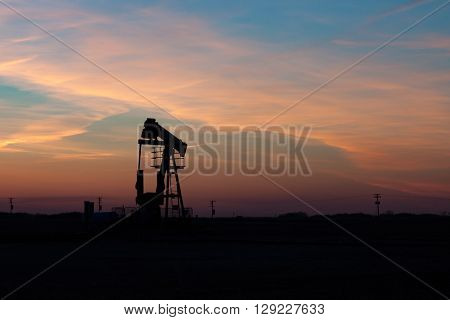 A single oil well pumpjack silhouetted against a prairie sunset