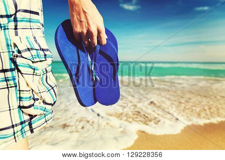 Man Holding His Sandals At The Shore