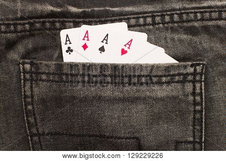 four ace cards inside gray jeans back pocket closeup