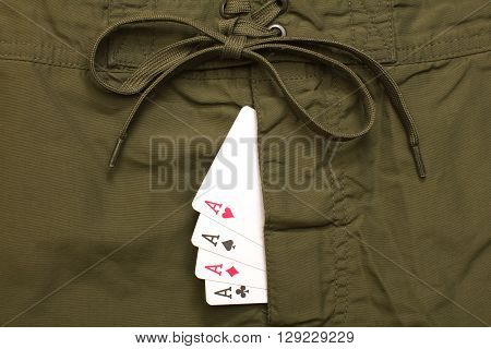 four ace cards inside green jeans fly closeup