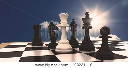 White queen standing with black chess pieces against bright blue sky with clouds