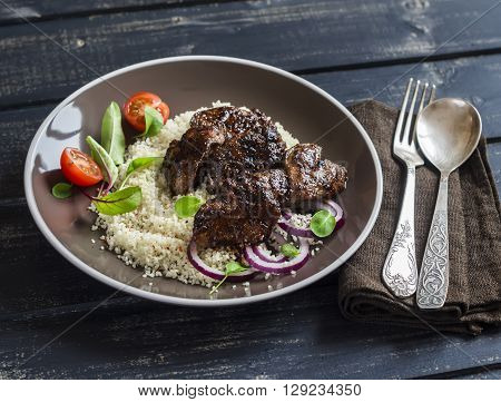 Grilled chicken liver couscous and fresh vegetable salad on a dark wooden background