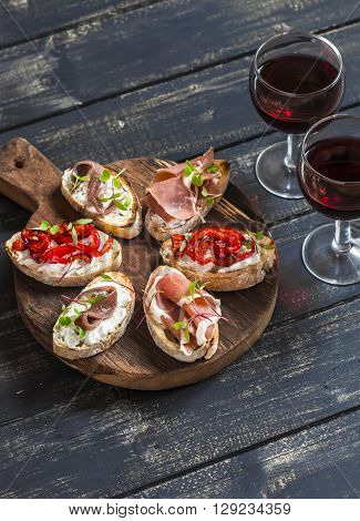 Sandwiches with goat cheese anchovies roasted peppers ham and two glasses of red wine on a wooden rustic board. Delicious snack or appetizer with wine