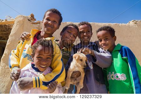 ASWAN, EGYPT - FEBRUARY 7, 2016: Local boys holding puppy in Nubian village on the Nile posing for camera.