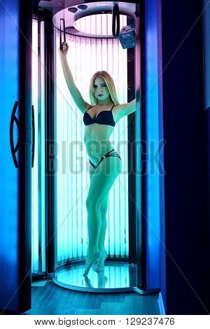 Image of attractive blond woman tans in tanning booth