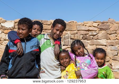 ASWAN, EGYPT - FEBRUARY 7, 2016: Group of local kids in Nubian village on the Nile posing for camera.