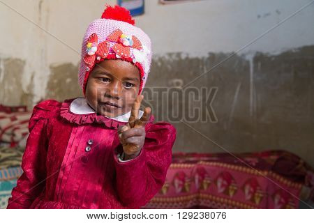 NUBIAN VILLAGE, EGYPT - FEBRUARY 7, 2016: Portrait of cute Nubian little girl in traditional clothes raising two fingers.
