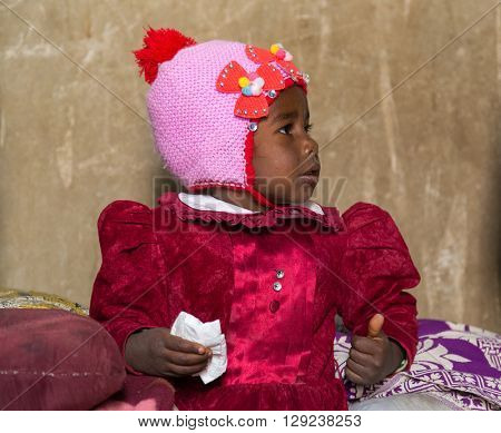NUBIAN VILLAGE, EGYPT - FEBRUARY 7, 2016: Portrait of cute Nubian little girl in traditional clothes.