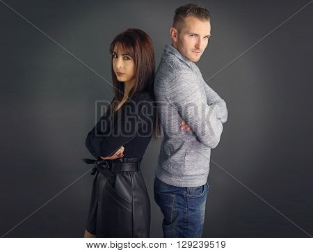 Young couple who sulks over a gray background