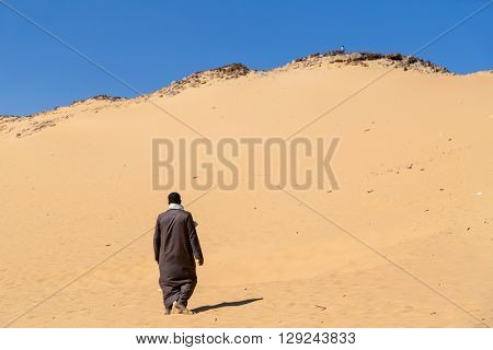 Nubian man wearing traditional clothing walking in sandy desert.