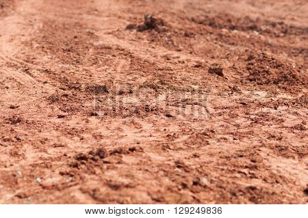 Plowed soil textured surface with grooves under bright sunlight
