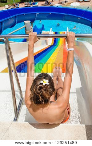 happy woman going down a water slide at a water park.