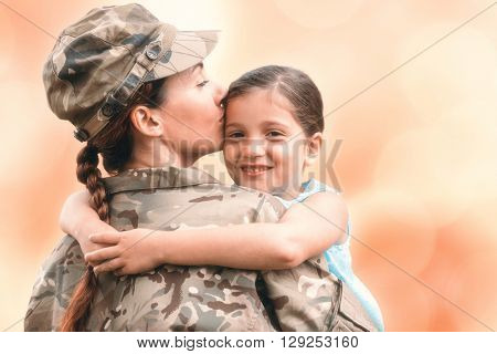Close-up of mother in army uniform kissing daughter against colorful background