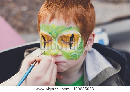 Child animator, artist's hand draws face painting to redhead child. Redhead boy with funny face painting. Painter makes reptile eyes at him. Children holiday, event, birthday party, entertainment.