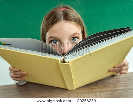 Surprised teenage girl with book. Photo of teen school girl creative concept Back to school