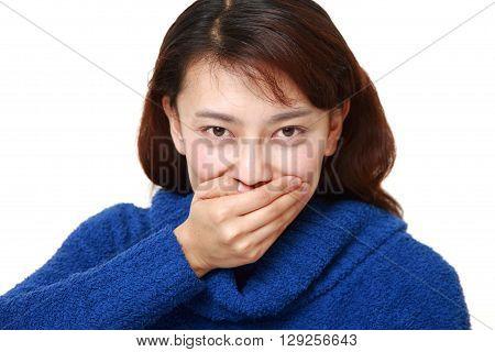 Asian woman making the speak no evil gesture