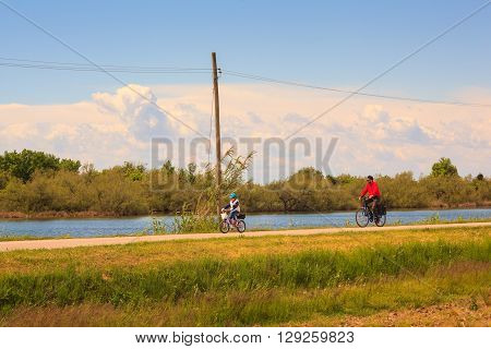 GRADO ITALY - APRIL 25: Dad and son cycling in the Nature reserve of the Isonzo river mouth on April 25 2016