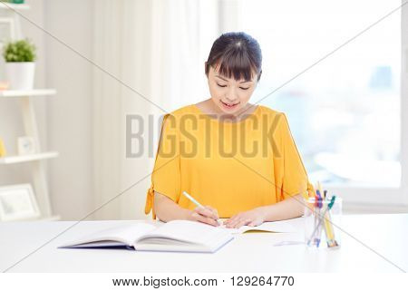 people, education, high school and learning concept - happy asian young woman student with book and notepad writing at home