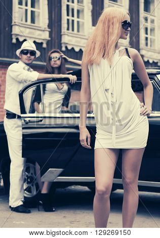 Happy young fashion blond woman in sunglasses next to retro car. Female fashion model in white dress