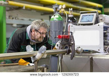 Industrial operator setting  computer controlled process of orbital welding machine in  stainless steel pipes manufacturing workshop.