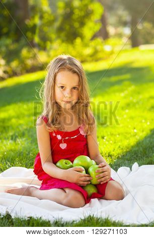 Portrait of a funny little girl with green apples in the summer park