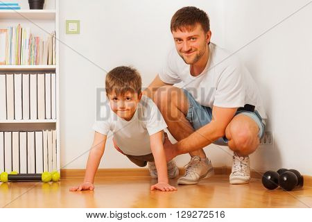 Cheerful father helping his kid son doing press-ups wearing blank white tees together at home