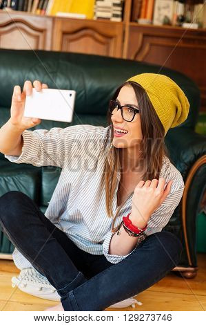 Pretty hipster girl taking selfie and laughing hard.
