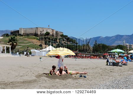 FUENGIROLA, SPAIN - JUNE 20, 2008 - Holidaymakers relaxing on the beach with Sohail castle to the rear Fuengirola Malaga Province Andalucia Spain Western Europe, June 20, 2008.