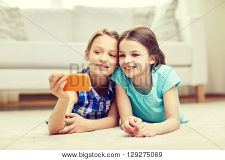 people, children, technology, friends and friendship concept - happy little girls lying on floor and taking selfie with smartphone at home