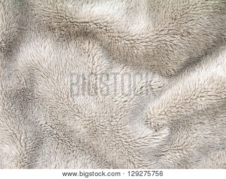 Beige folded fluffy polyester cozy fleece fabric background