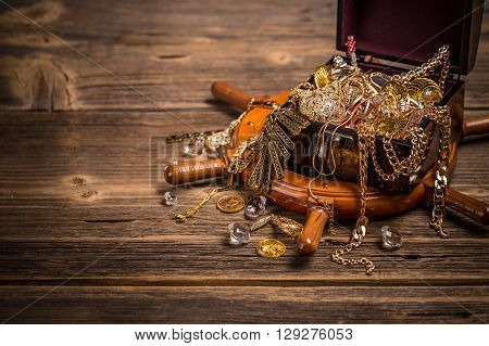 Pirates chest with golden jewelry on wooden background