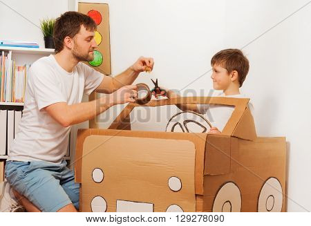 Dad helping his kid son to cut piece of sticky tape for fixing it to big toy cardboard car at home
