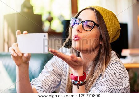 Pretty hipster girl taking selfie and making duck face, sending air kiss.