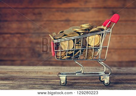Shopping cart and coins on old wood background. Toned image.