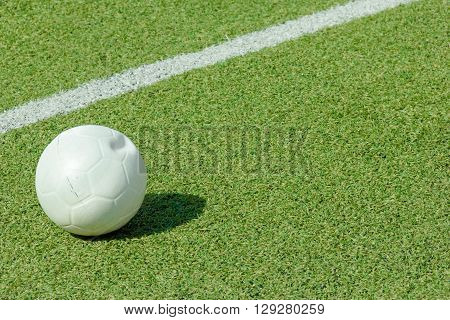 ball on green synthetic grass sports field with white line shot
