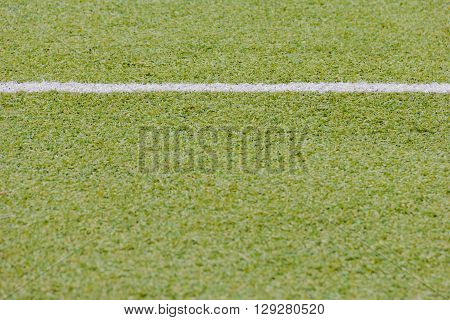green synthetic grass sports field with white line shot
