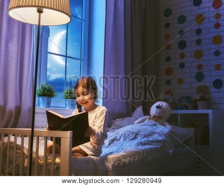 Cute little child girl reading a book under a lamp. Kid girl sitting in her bed on a dark moonlit night.